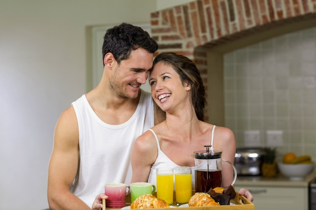 Happy couple holding a tray of breakfast in kitchen