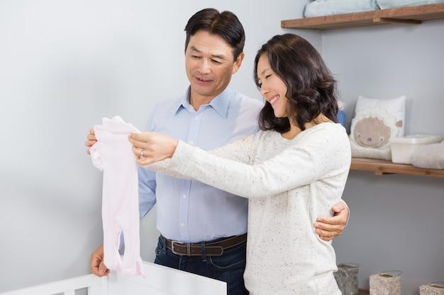 Happy couple holding white onesie near a crib