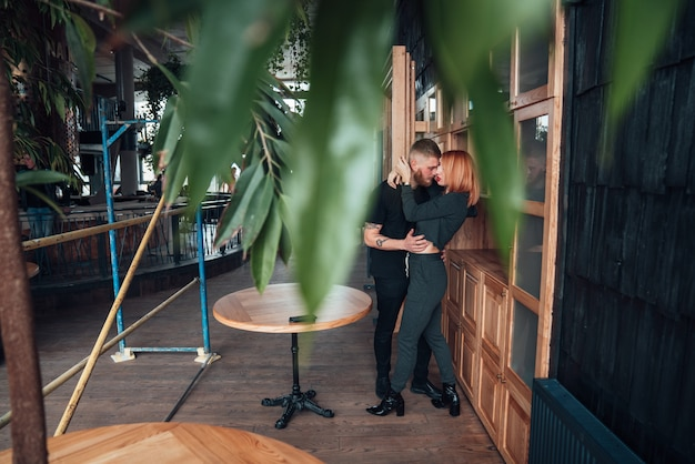 Happy couple hugging against a door with blurred tropical leaves