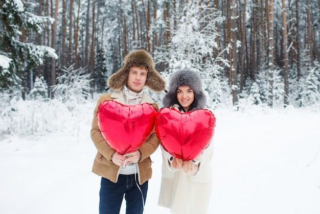 Счастливая пара обниматься и целоваться на открытом воздухе в зимнем лесу. воздушные шары в форме сердца