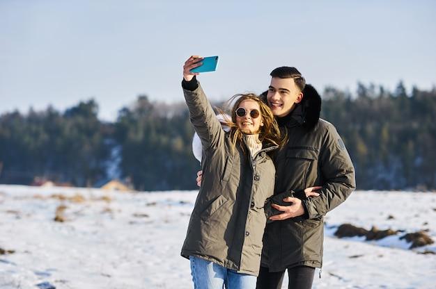 冬に屋外で抱き締めて笑う幸せなカップル。写真は防寒着の宣伝に適しています