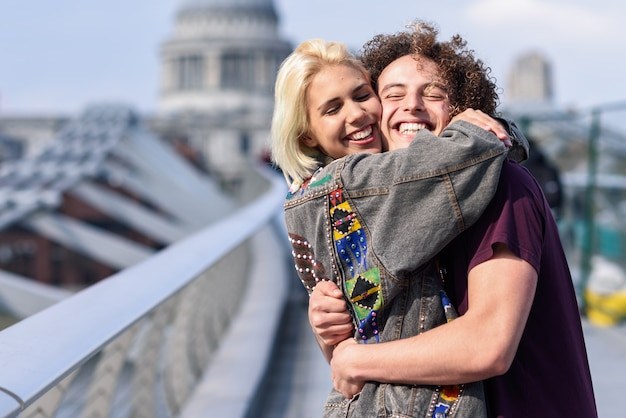 Happy couple hugging by millennium bridge, river thames, london.
