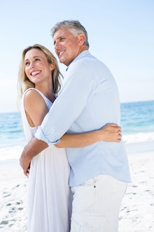 Happy couple hugging each other by the sea