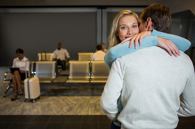 Счастливая пара, обнимая друг друга в зоне ожидания