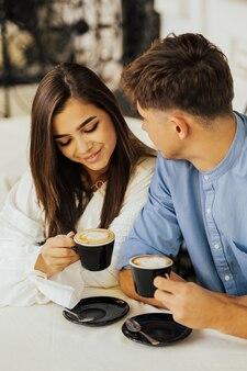 屋外カフェで抱き締める幸せなカップル。