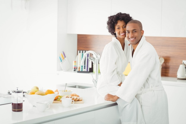 Happy couple hugging in the kitchen at home