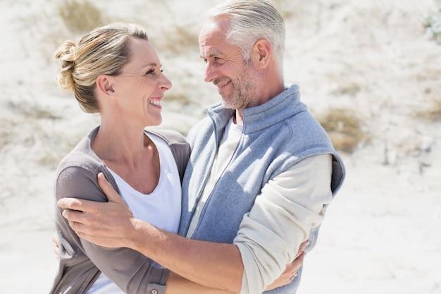 お互いを見てビーチで抱き合っている幸せなカップル