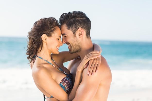 ビーチで抱き締める幸せなカップル