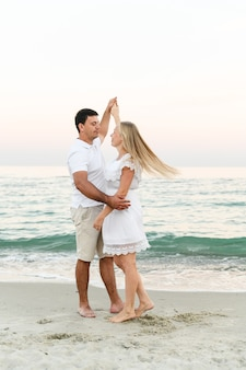 海岸で抱き締める幸せなカップル。ロマンチックな時間。幸せな若者。