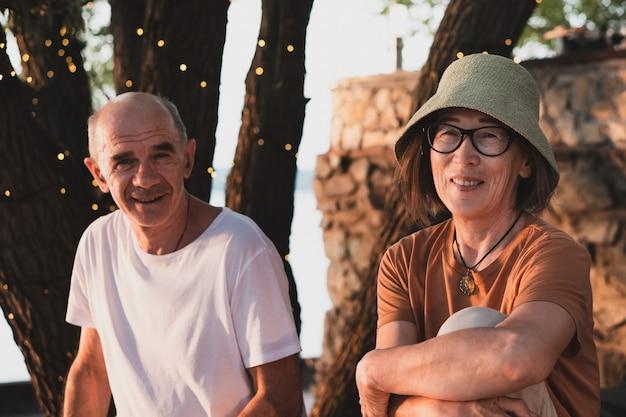 都市公園の大きなおとぎ話の木の下に座っている幸せなカップルの夫と妻