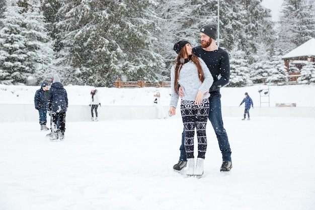Happy couple in ice skates hugging and looking at each other outddors with snow on background