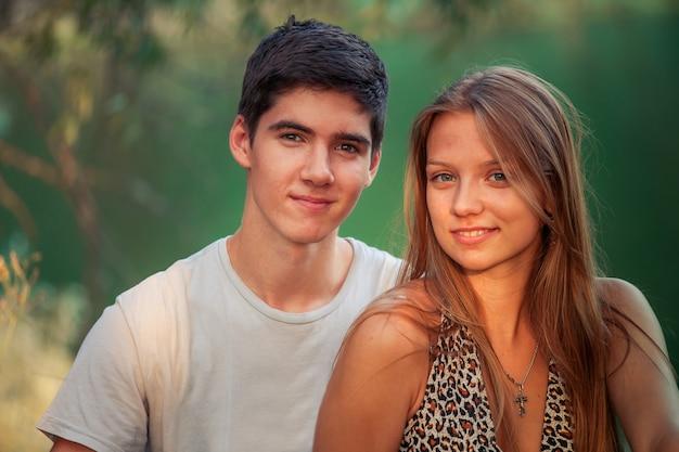 愛の幸せなカップルは一緒に幸せで笑顔です。男と女は夏に水辺に座っています。バレンタインデーのコンセプト