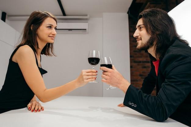 愛の幸せなカップルは、手にワインとグラスを祝って保持しています。高品質の写真