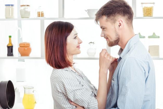 Счастливая пара в любви, готовя тесто на кухне