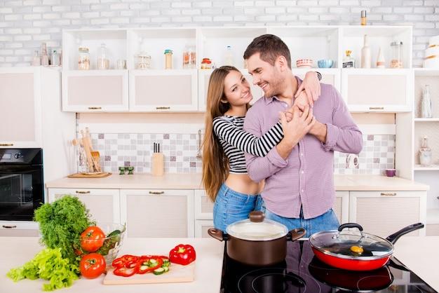 キッチンで料理とハグを愛する幸せなカップル