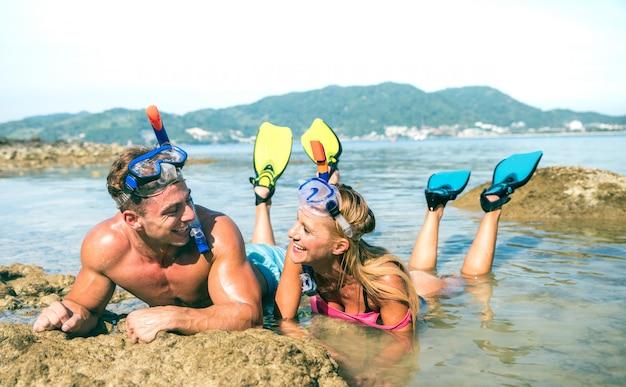 シュノーケルマスクとフィンとタイの熱帯のビーチで楽しんで恋に幸せなカップル