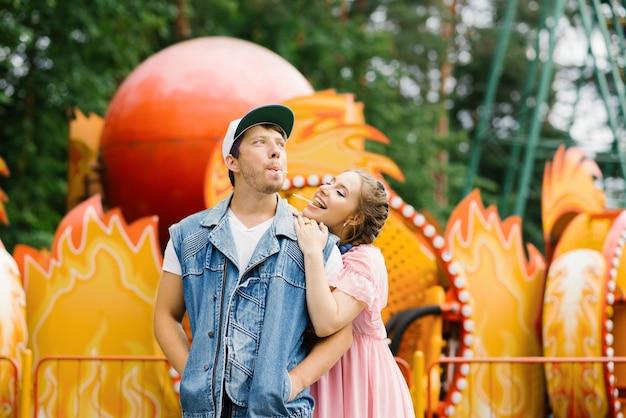 Счастливая влюбленная пара веселится в парке развлечений и ест леденцы