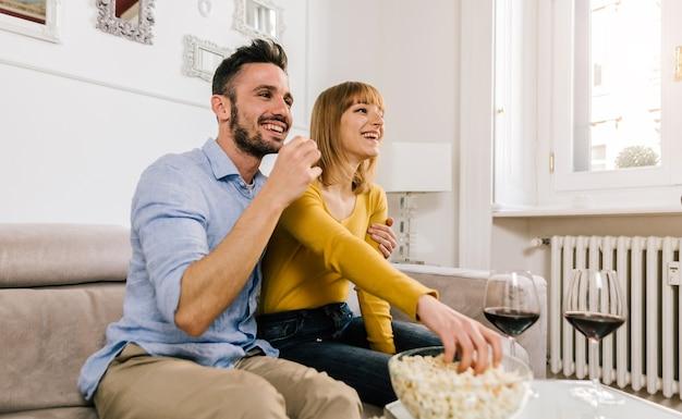 Счастливая влюбленная пара весело сидит на диване у себя дома
