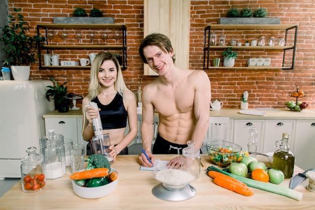 健康的なジュースを作るキッチンで恋の幸せなカップル。バナナと牛乳をブレンドして健康的なスムージーを作る女性と男性がカロリーを計算します。