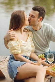 愛の幸せなカップルは美しい場所で夏の日にピクニックにキスしています。幸福と静けさ。休息と楽しみ。美しい瞬間。スーパーデイ。ロマンチックな関係。優しさとケア。