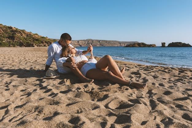 恋に幸せなカップルは、日没や日の出の間にビーチに座っています。