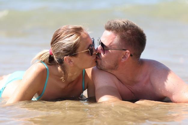 Счастливая влюбленная пара лежит на животе в воде.