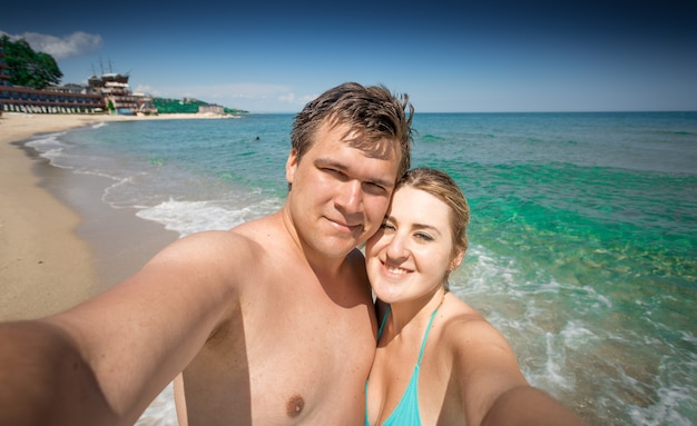 Счастливая влюбленная пара, делающая селфи на берегу моря в солнечный день