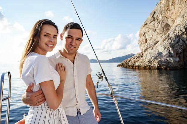 Счастливая влюбленная пара на яхте летом на романтических каникулах