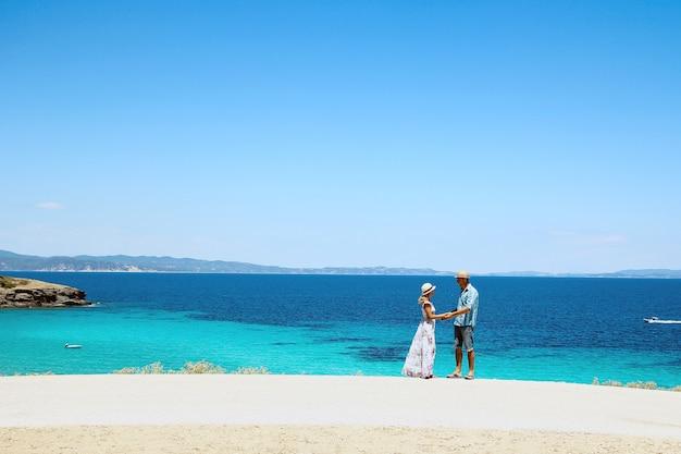 여름 휴가에 그리스의 푸른 바다 근처 해변에서 사랑에 빠진 행복한 커플