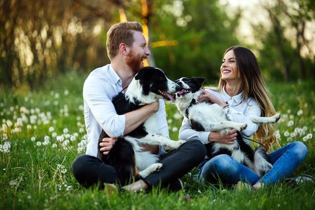 Счастливая влюбленная пара, играя с собаками в парке на открытом воздухе