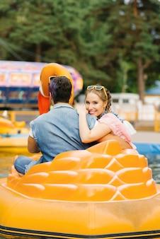 Счастливая влюбленная пара, катающаяся на водной аттракционе в парке развлечений