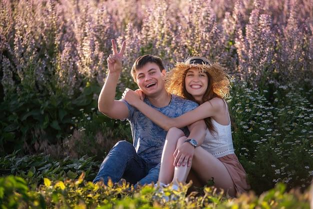 愛の幸せなカップルは、咲くセージフィールドに抱き締めて座っています。麦わら帽子をかぶった美しい少女を持つ若い男は、楽しんで、浮気し、手を振って、舌を見せています。狂った恋人たちの旅