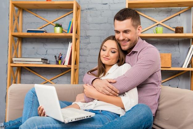 Счастливая влюбленная пара, сидя на диване с ноутбуком и делая покупки
