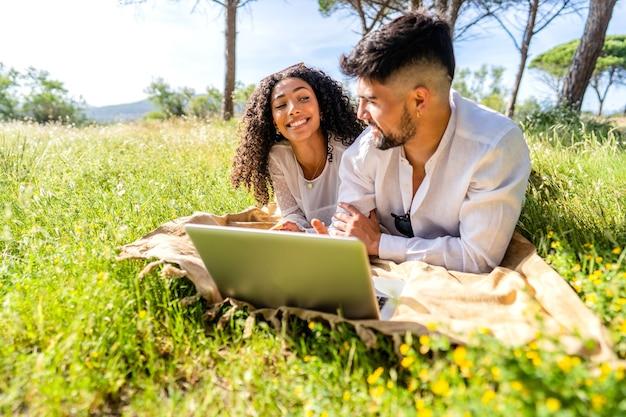ソーシャルネットワークで休暇を共有する芝生のフィールドに横たわって自然の中でラップトップを使用して恋に幸せなカップル