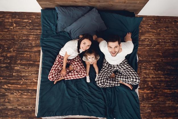 パジャマ姿で幸せなカップルは、小さな女の子と一緒にベッドに座る。