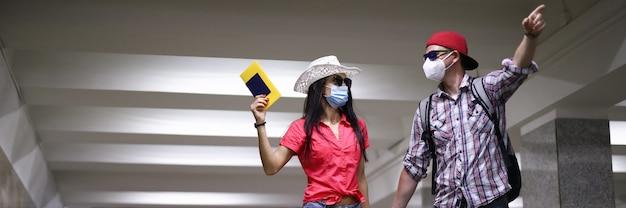 防護マスクで幸せなカップルはアーポートターミナルのトンネルに行き、ポートレートを手に持ってください。 covid 19コンセプトの後の旅行