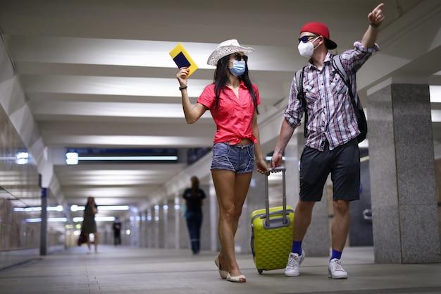 防護マスクで幸せなカップルがアーポートターミナルのトンネルに行き、ポートレートを手に持って