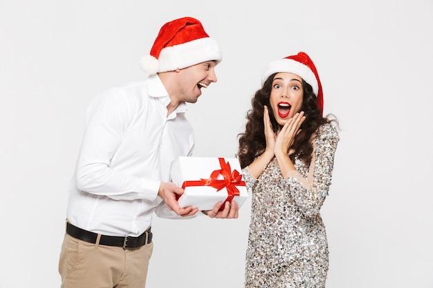 白で隔離された新年を祝う赤い帽子をかぶった幸せなカップル、プレゼントと交換