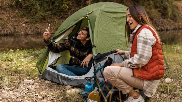 Счастливая пара в лесу, делая самостоятельные фотографии
