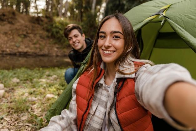 Счастливая пара в лесу, делающая селфи