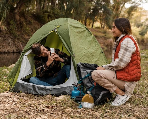 Счастливая пара в лесу фотографирует