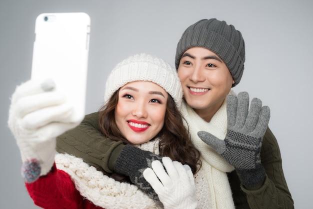 스마트폰으로 사진을 찍는 겨울 옷을 입은 행복한 커플