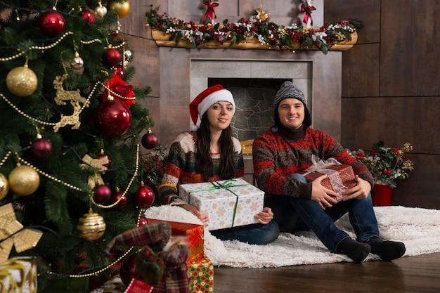 따뜻한 스웨터를 입은 행복한 커플과 크리스마스 트리 근처에 장식된 벽난로 앞 양탄자에 앉아 선물을 들고 재미있는 겨울 모자
