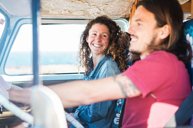 Happy couple inside minivan doing a road trip - woman with freckles having fun on summer vacation traveling with her boyfriend