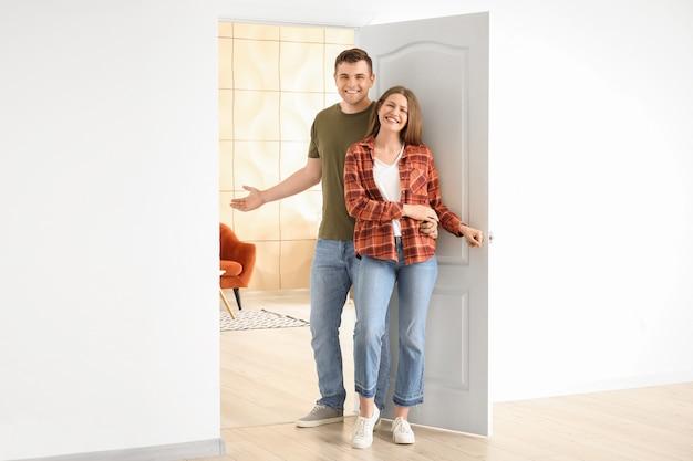 彼らの新しい家でゲストを招待する幸せなカップル