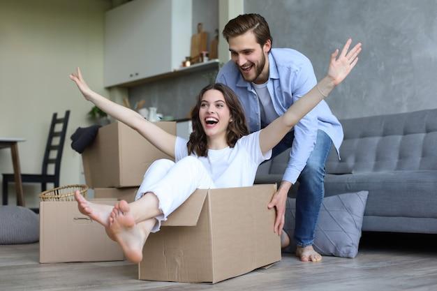 행복한 커플은 이사하는 날 새 집에서 판지 상자를 가지고 즐겁게 놀고 있고, 여자는 남자가 그것을 밀고 있는 동안 판지 상자에 앉아 있습니다.