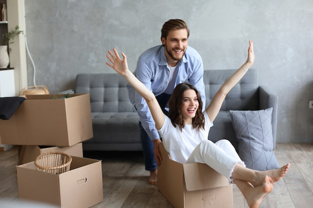 Счастливая пара развлекается с картонными коробками в новом доме в день переезда, женщина верхом сидит в картонной коробке, пока мужчина ее толкает.