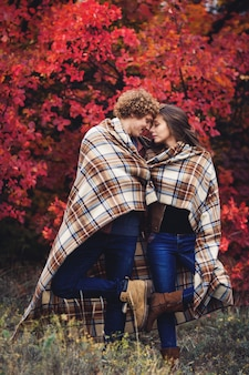 Happy couple is hiding behind plaid autumn day against red trees.