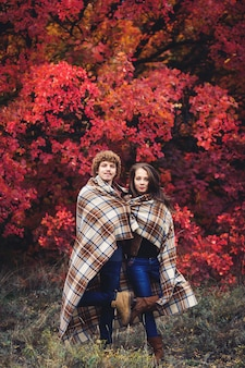 Happy couple is hiding behind plaid autumn day against of red trees