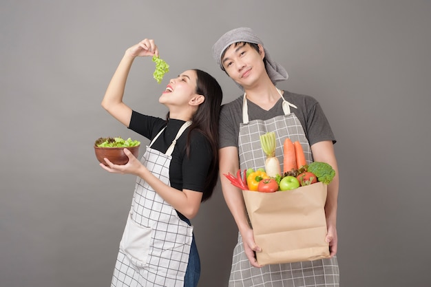 Happy couple is holding vegetables in grocery bag grey  wall
